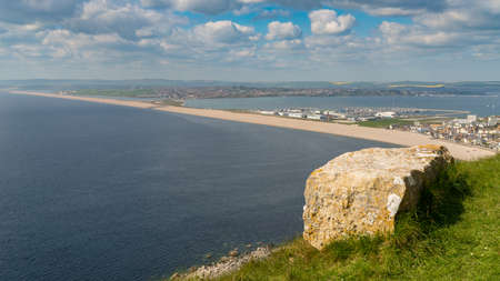 View from the South West Coast Path  towards Fortuneswell and Chesil Beach, Isle of Portland, Jurassic Coast, Dorset, UK - with clouds over Weymouth in the background