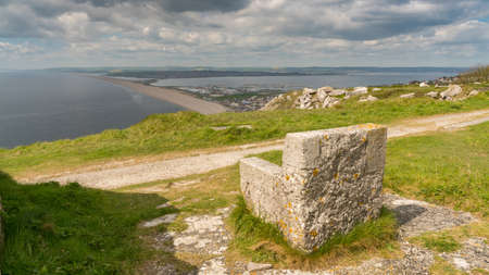 A stone seat on the South West Coast Path  with view towards Fortuneswell and Chesil Beach, Isle of Portland, Jurassic Coast, Dorset, UK - with clouds over Weymouth in the background