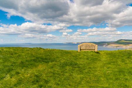 Stone bench at the South West Coast Path with a view over the Jurassic Coast, Dorset, UK