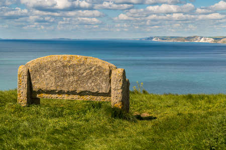 Stone bench at the South West Coast Path with a view over the Jurassic Coast, near Worth Matravers, Jurassic Coast, Dorset, UK