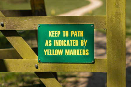 Sign: Keep to path as indicated by yellow markers, seen in Tyneham Village, Jurassic Coast, Dorset, UK
