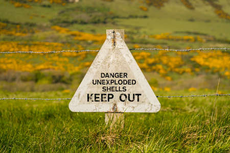 Sign: Danger unexploded shells keep out, seen on the South West Coast Path between Worbarrow Bay and Brandy Bay, Jurassic Coast, Dorset, UK