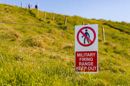Sign: Military firing range keep out, seen at Worbarrow Bay, Jurassic Coast, Dorset, UK - with two blurry people in the background ignoring the sign