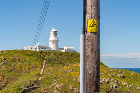 Sign: Danger of death keep off (English & Welsh) with Strumble Head Lighthouse, near Goodwick, Pembrokeshire, Dyfed, Wales, UK
