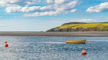Een boot en sommige boeien bij Pembrokeshire-kust in Parrog, Dyfed, Wales, het UK Stockfoto