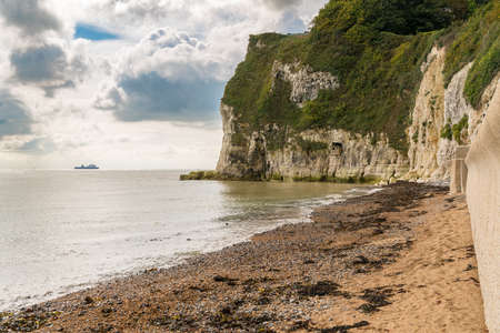 White cliffs and beach on the British Channel coast of St Margarets at Cliffe near Dover, Kent, England, UK - with a ferry in the background Stock Photo