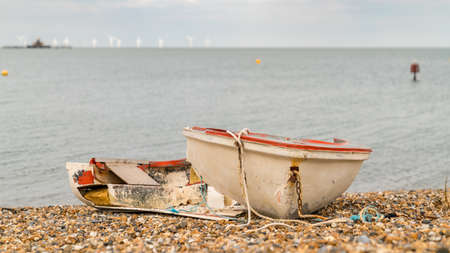 A broken boat on the pebble beach of Herne Bay, Kent, England, UK - with wind turbines in the background