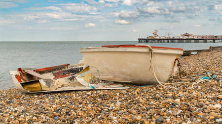 A broken boat on the pebble beach of Herne Bay, Kent, England, UK - with Herne Pier in the background