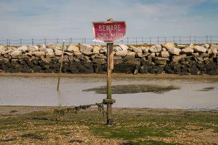 Teken: Pas op voor zachte modder, gezien in Herne Bay, Kent, Engeland, Verenigd Koninkrijk - met Neptunes Arm op de achtergrond