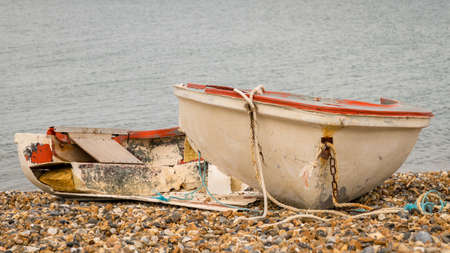 A broken boat on the pebble beach of Herne Bay, Kent, England, UK