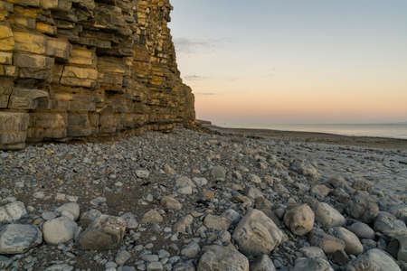 The stones and cliffs of Llantwit Major Beach in the evening light, South Glamorgan, Wales, UK