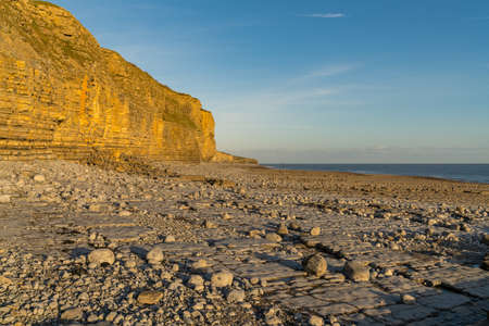 The stones and cliffs of Llantwit Major Beach in the evening sun, South Glamorgan, Wales, UK - with the Bristol Channel in the background