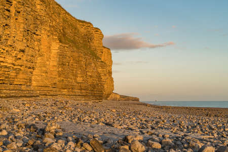 The stones and cliffs of Llantwit Major Beach in the evening sun with some clouds over the cliffs, South Glamorgan, Wales, UK