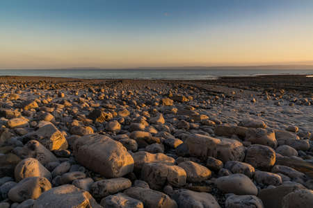 The stones of Llantwit Major Beach with the Bristol Channel in the evening light, South Glamorgan, Wales, UK