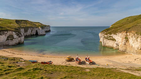 Fishing boats and crawler on the beach of Flamborough North Landing near Bridlington, East Riding of Yorkshire, UK