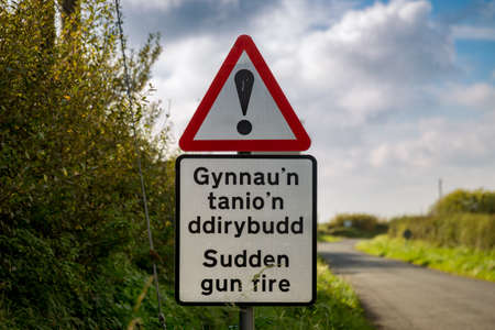 Sign: Sudden gun fire (Welsh & English), seen near Castlemartin in Pembrokeshire, Wales, UK
