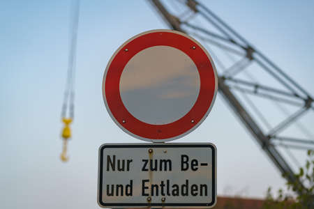 Symbol: No vehicles, Text: Only for loading and unloading (German), with a blurry crane in the background, seen in Duisburg-Ruhrort, North Rhine-Westphalia, Germany