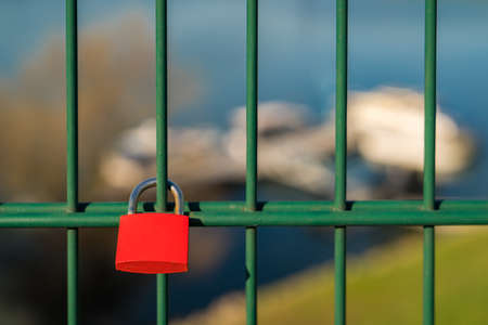 Love lock and grid of the lift bridge Walsum in Duisburg, North Rhine-Westphalia, Germany - with some blurry boats in the background