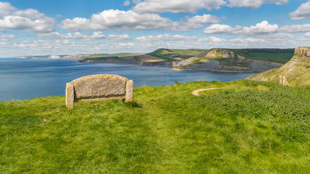 Stone bench at the South West Coast Path with a view over the Jurassic Coast and Emmetts Hill, near Worth Matravers, Jurassic Coast, Dorset, UK