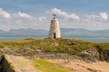Tower Bach Lighthouse at Ynys Llanddwyn in Anglesey, Gwynedd, Wales, UK - with Snowdonia mountain range in the background