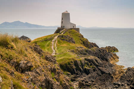 Tower Mawr Lighthouse at Ynys Llanddwyn in Anglesey, Gwynedd, Wales, UK - with Snowdonia mountain range in the background Stock Photo