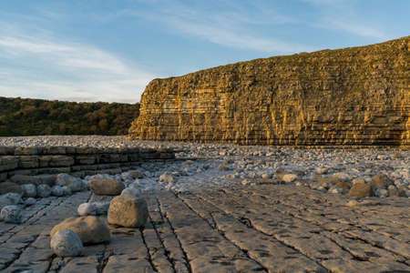 The stones and cliffs of Llantwit Major Beach in the evening sun, South Glamorgan, Wales, UK Banco de Imagens