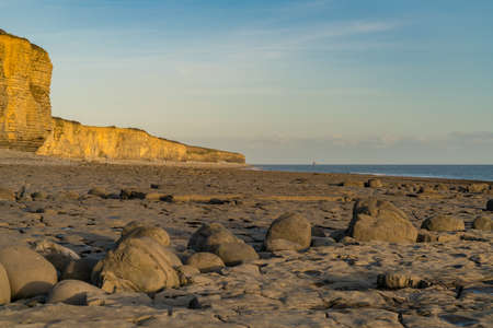 The stones and cliffs of Llantwit Major Beach in the evening sun, South Glamorgan, Wales, UK Stock Photo