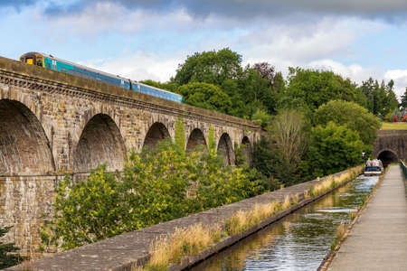Chirk, Wrexham, Wales, UK - August 31, 2016: People steering a narrowboat over the Chirk Aqueduct towards the Chirk Tunnel, with a train passing the Viaduct Stok Fotoğraf - 104860955