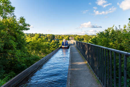 Near Froncysyllte, Wrexham, Wales, UK - August 30, 2016: People stering a Narrowboat over the Pontcysyllte Aqueduct, seen from the Froncysyllte side