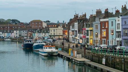 Weymouth, Dorset, England, UK - April 21, 2017: Evening view from the Town Bridge, with fishing boats on the shore and people on the sidewalks