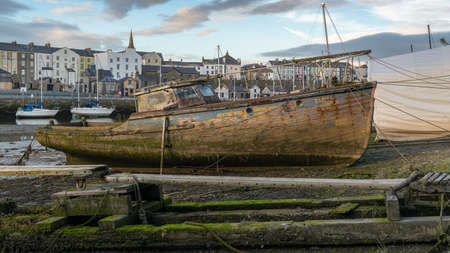 Caernarfon, Gwynedd, Wales, UK - June 15, 2017: Old dirty boat at the shore of Afon Seiont with new boats and some houses in the background Editorial
