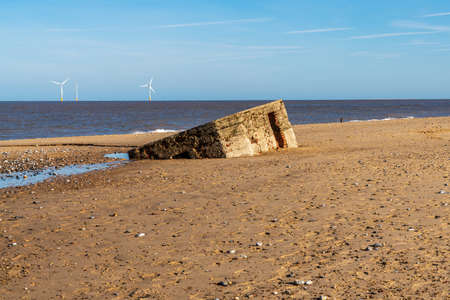 old bunker on the beach and wind turbines in the background