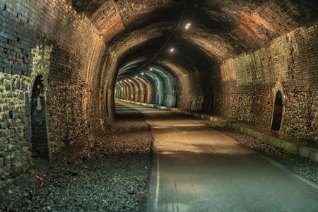 Walking through the Headstone Tunnel, near Monsal Head in the East Midlands, Derbyshire, Peak District, England, UK