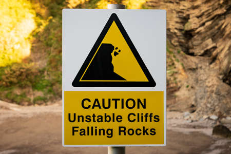 Sign: Caution, unstable cliffs falling rocks, seen in Ilfracombe, Devon, England, UK