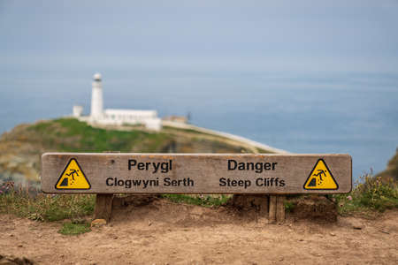 Near Holyhead, Anglesey, Gwynedd, Wales, UK - June 08, 2018 - Sign Danger steep cliffs (Welsh & English) with South Stack Lighthouse in the background Editorial