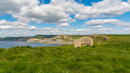 Stone bench at the South West Coast Path with a view over the Jurassic Coast and Emmett's Hill, near Worth Matravers, Jurassic Coast, Dorset, UK