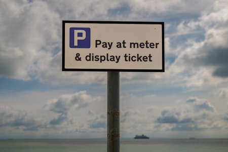 Sign: Pay at meter & display ticket, seen in St Margarets at Cliffe, Kent, England, UK - with clouds and a ferry crossing the British channel in the background Stock fotó