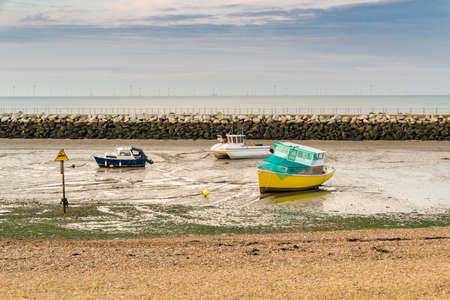 Boats at low tide near Neptunes Arm in Herne Bay, Kent, England, UK