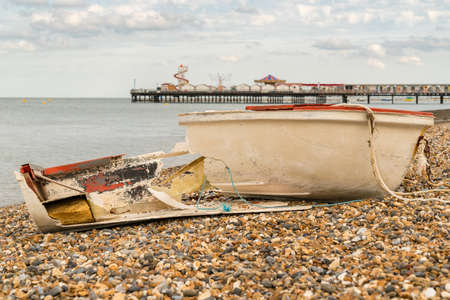 A broken boat on the pebble beach of Herne Bay, Kent, England, UK - with Herne Pier in the background Imagens