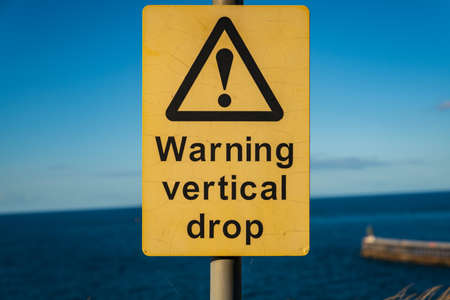 Sign: Warning vertical drop, seen in Whitby, North Yorkshire, England, UK