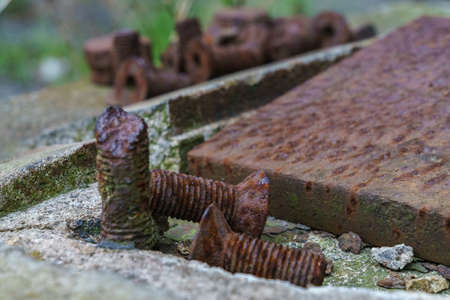 Some rusty screws on a slab of concrete