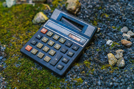 An old calculator on a dirty floor Stock Photo