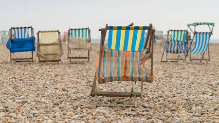 Empty deck chairs on a pebble beach Stock Photo