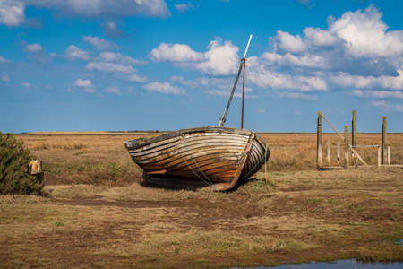 An old wooden sailing boat in Thornham Old Harbour, Norfolk, England, UK