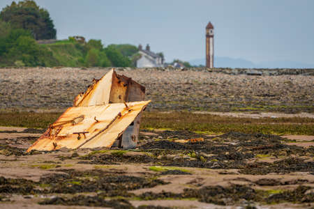 A rusty part of a  shipwreck in the mud of the Walney Channel with the Rampside Lighthouse in the background, seen from the road to Roa Island, Cumbria, England, UK 写真素材