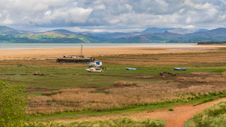 Boats in the grass, with clouds over the Lake District National Park in the background, seen in Askam-in-Furness, Cumbria, England, UK