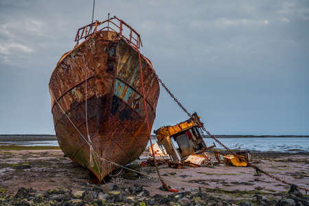 A rusty shipwreck in the mud of the Walney Channel, seen from the road to Roa Island, Cumbria, England, UK