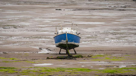 A boat in the mud of the Walney Channel, seen from the road to Roa Island, Cumbria, England, UK 写真素材