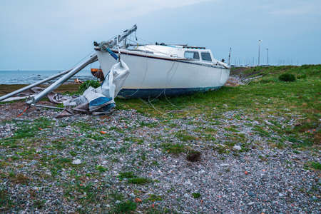 A damaged boat in the low tide, seen from the road to Roa Island, Cumbria, England, UK