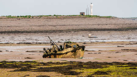 A damaged boat in the mud of the Walney Channel, seen from the road to Roa Island, Cumbria, England, UK - with a lighthouse in the background 写真素材